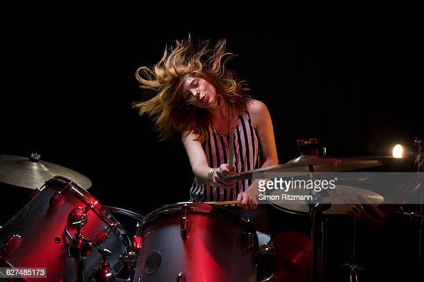 Young woman plays drums with enjoyment