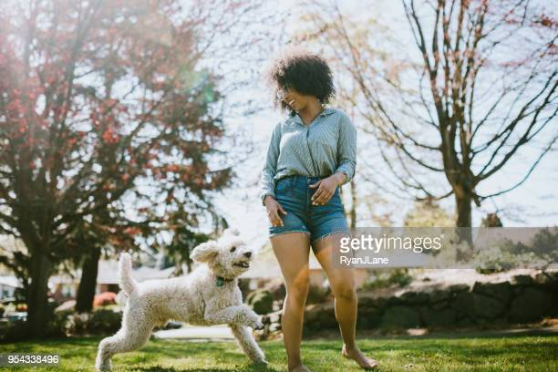 a young woman plays outside with pet poodle dog - denim shorts stock pictures, royalty-free photos & images