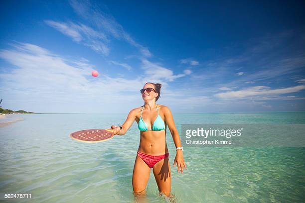 A young woman plays racquetball on the beach.
