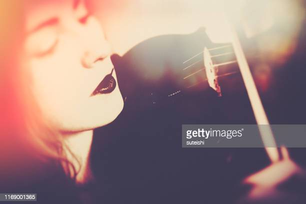 young woman plays violin - stringed instrument stock pictures, royalty-free photos & images