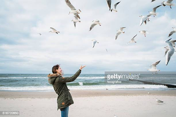 young woman plays with seagulls at the baltic
