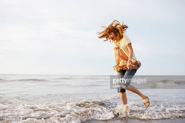 Young woman plays with wave on the beach