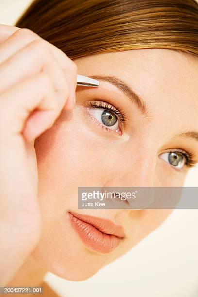 Young woman plucking eyebrow with tweezers, close-up