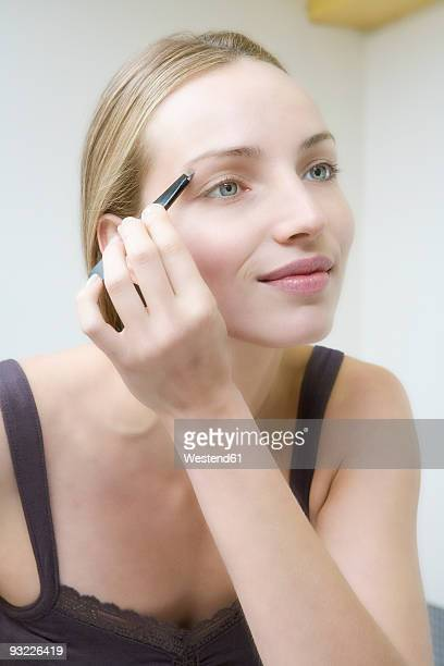 Young woman plucking eyebrows, close up