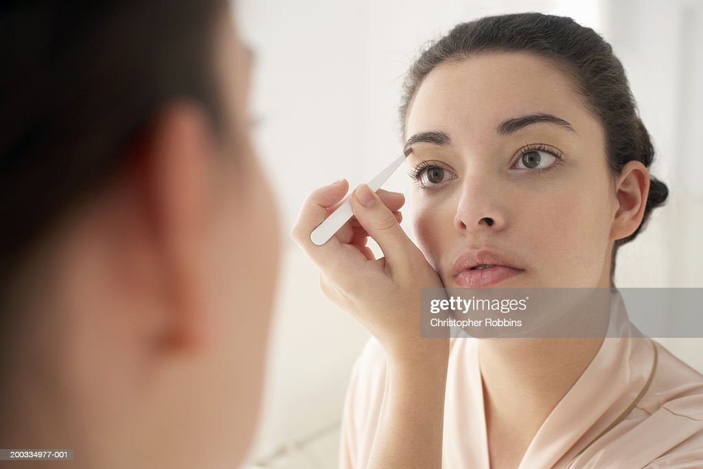 Young woman plucking eyebrows, close-up, reflection in mirror : 圖庫照片