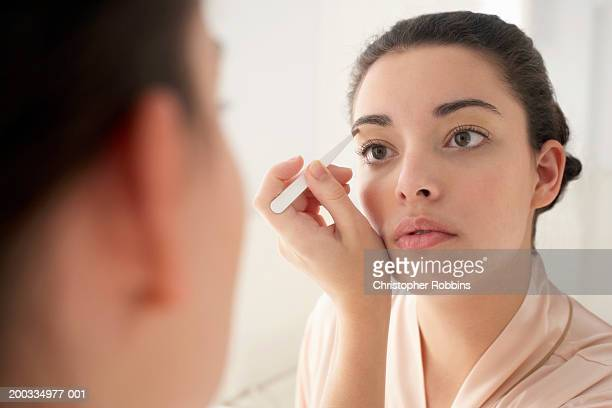 young woman plucking eyebrows, close-up, reflection in mirror - 眼眉 個照片及圖片檔
