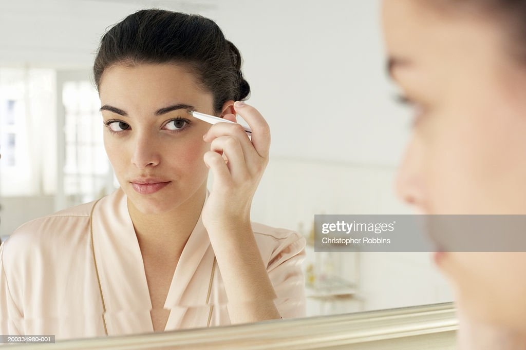Young woman plucking eyebrows, close-up, reflection in mirror : Stock Photo