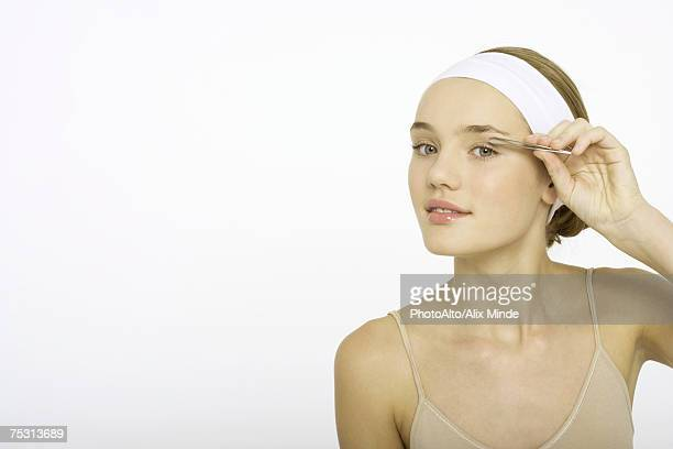 young woman plucking eyebrows - epilation maillot photos et images de collection