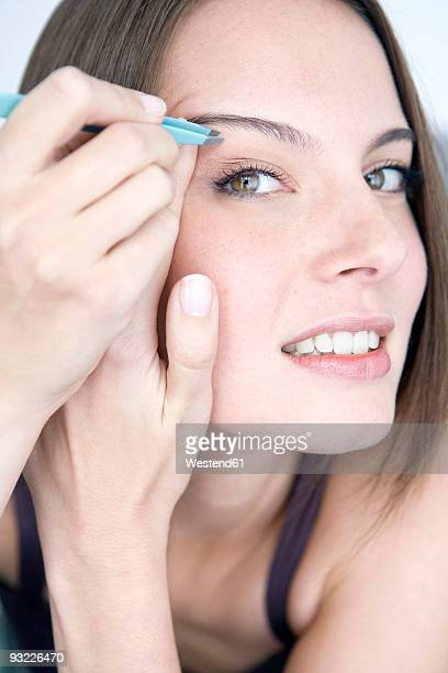 Young woman plucking her eyebrows, portrait, close-up