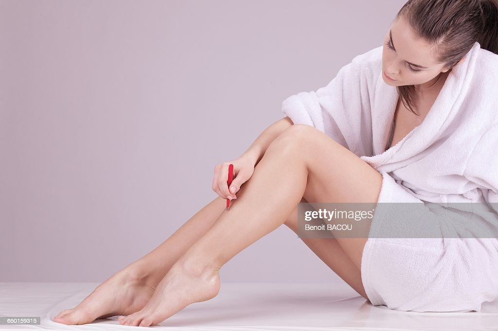 Young woman plucking with tweezers : Stock Photo