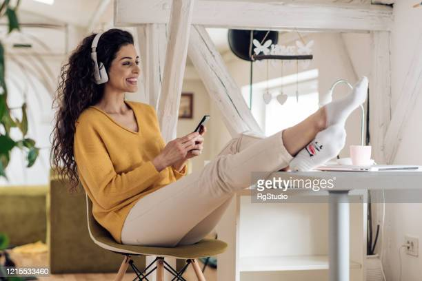 young woman podcasting during coronavirus quarantine - podcasting stock pictures, royalty-free photos & images