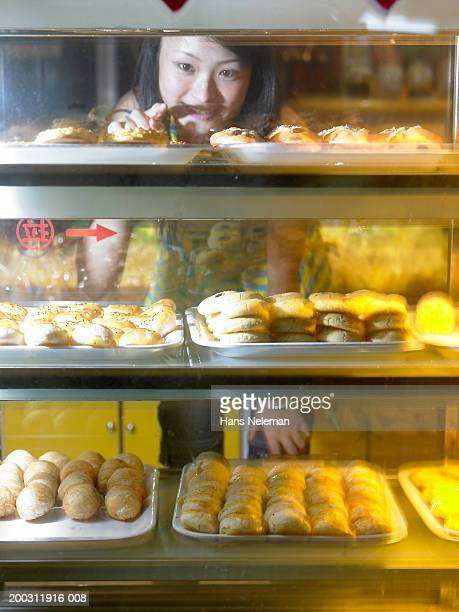 Young woman pointing at pastry in display case
