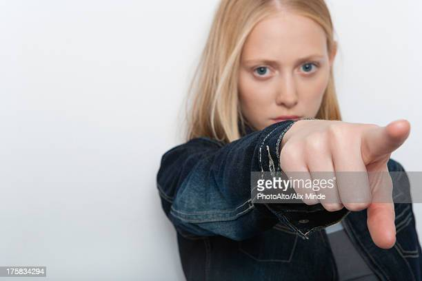 Young woman pointing finger accuslingly