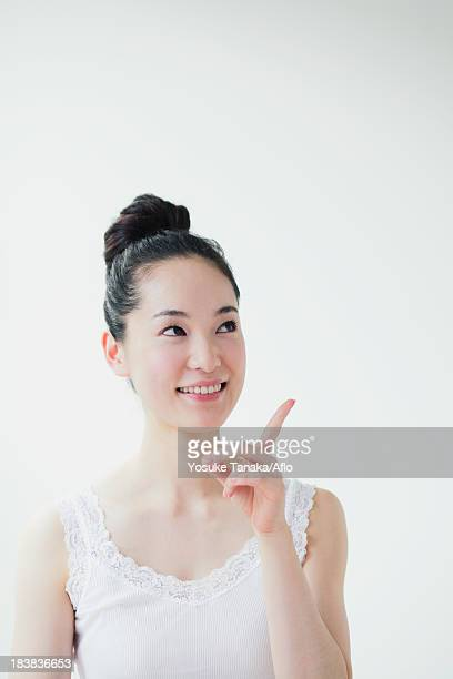 Young woman pointing finger up smiling