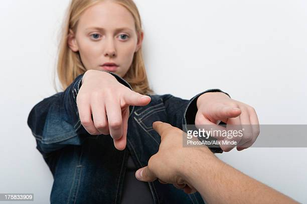 Young woman pointing fingers accusingly at person in foreground