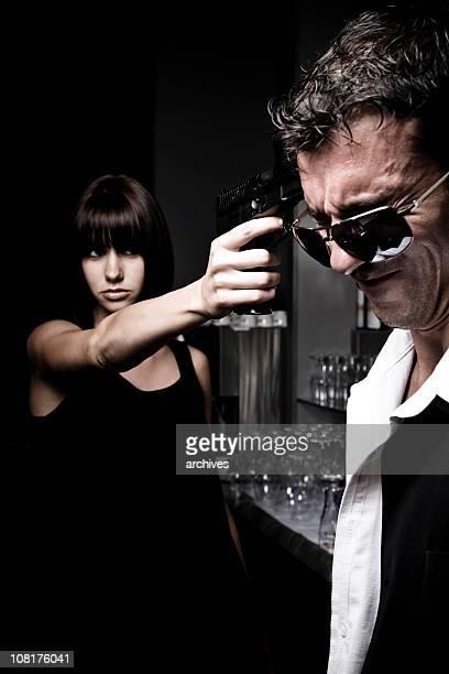 Junge Frau zeigt Waffe im Kopf von Grimassieren Mann