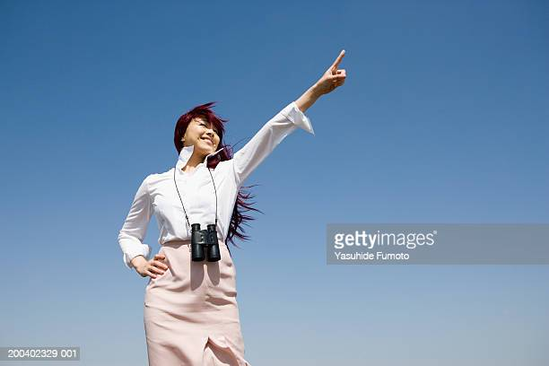 Young woman pointing into air, wearing binoculars, low angle view