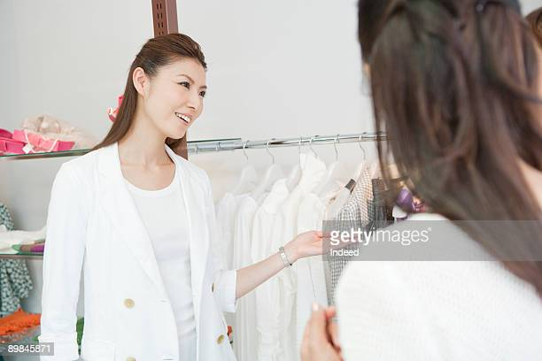 Young woman pointing shirts for customer