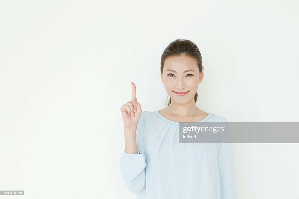 Young woman pointing upward : Stock Photo