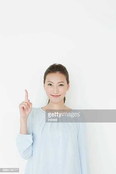 young woman pointing upward - 上半身 ストックフォトと画像