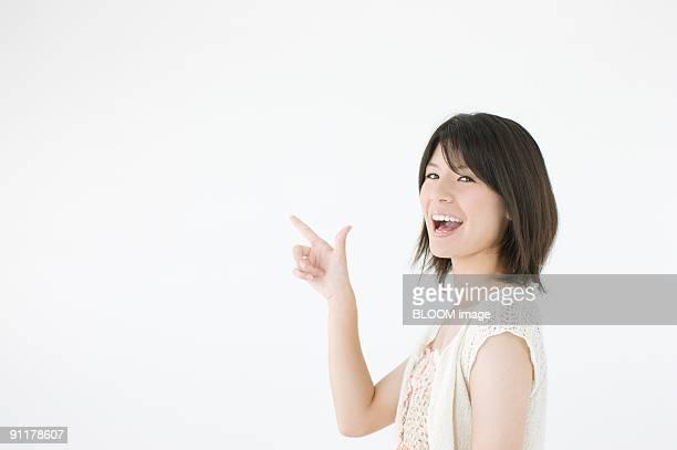 Young woman pointing upward, studio shot