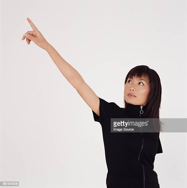 Young woman pointing upwards