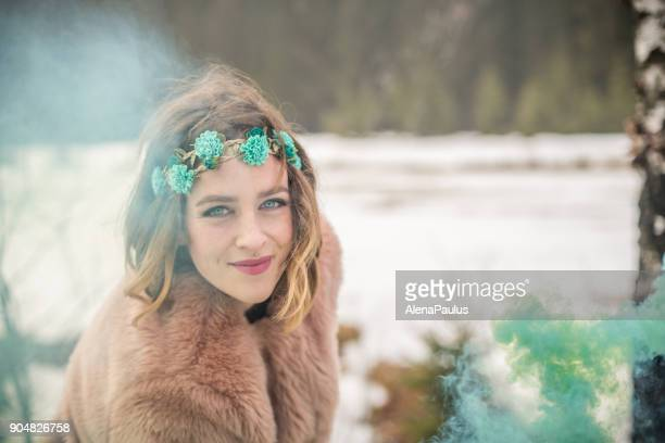 Young woman portrait outdoors with green smoke bomb