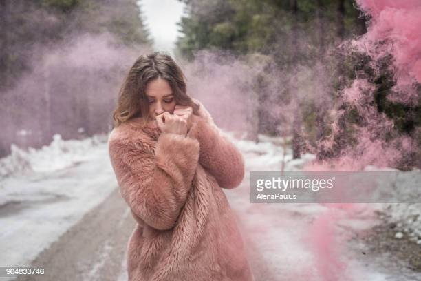 Young woman portrait outdoors with pink smoke bomb