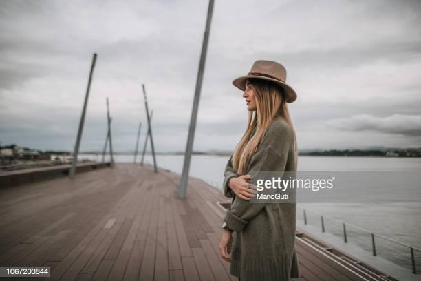 young woman portrait with hat by the sea - coat imagens e fotografias de stock
