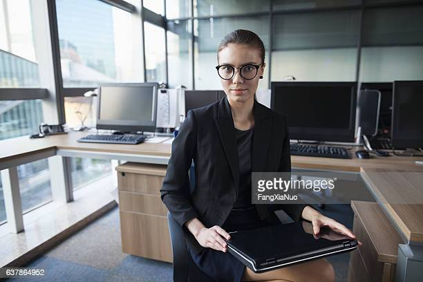 Young woman portrait with laptop in business office