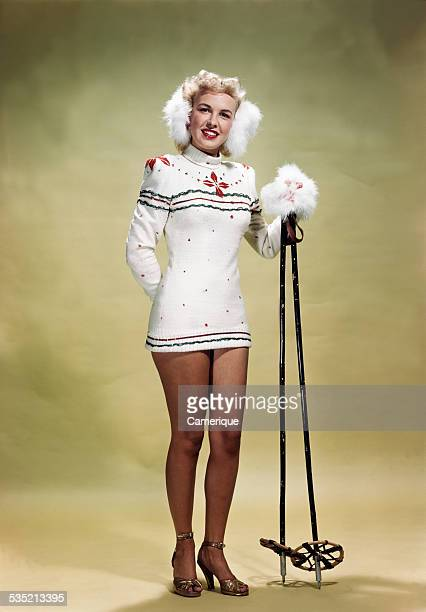 Young woman posed in a skimmpy winter outfit with earmuffs and ski poles in hiheels Los Angeles California 1950s