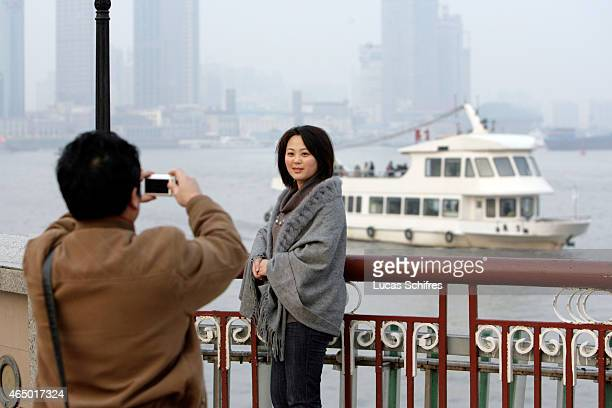 A young woman poses for a photograph on the famous 'Bund' waterfront on January 8 2009 in Shanghai China