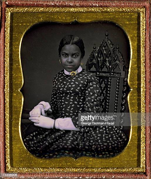 A young woman poses for a portrait as she sits in a chair with an elaborately carved back in this daguerreotype with applied color and a color frame...