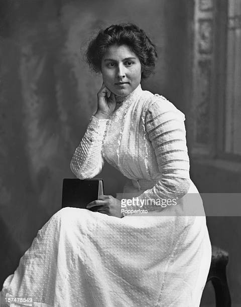 A young woman poses for a portrait in a white fulllength dress circa 1905 The picture was taken by photographer Henry Mayson at his studio in Keswick...