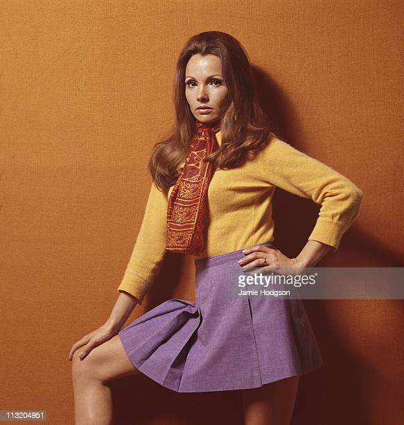 A young woman poses in a purple pleated miniskirt with a yellow top and an orange patterned scarf circa 1970