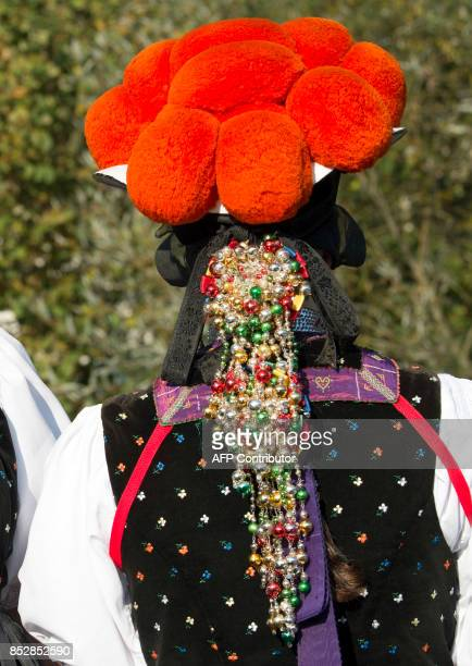 A young woman poses in a traditional dress of the Black Forest region with the red Bollenhut in Gutach southern Germany on September 24 2017 / AFP...