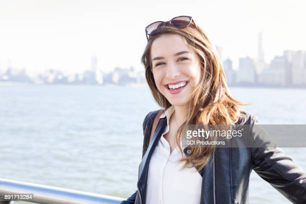 Young woman poses on pier overlooking city skyline