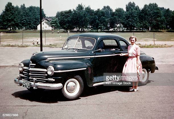 Young woman poses with her Plymouth automobile ca 1951
