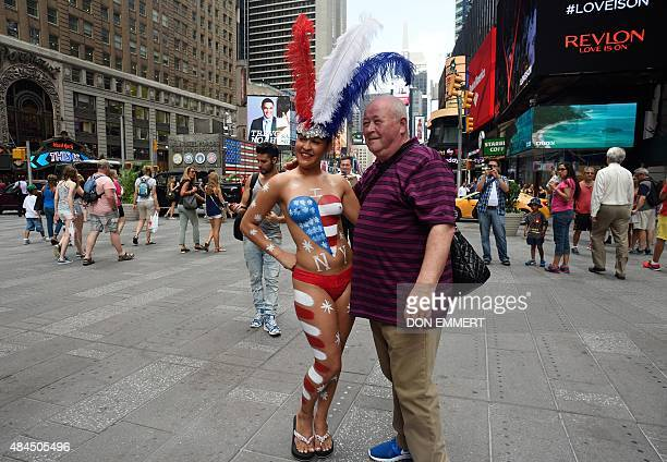 A young woman poses with tourists in Times Square wearing body paint to cover herself August 19 2015 in New York Mayor Bill de Blasio said that he...