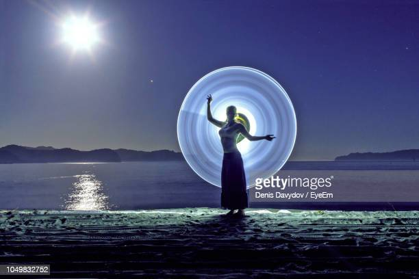 young woman posing against light painting at beach - lichtmalerei stock-fotos und bilder