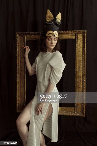 young woman posing against picture frame on wall - mask cartoon characters stock pictures, royalty-free photos & images