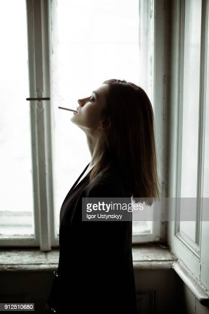 young woman posing against window - beautiful women smoking cigarettes stock pictures, royalty-free photos & images