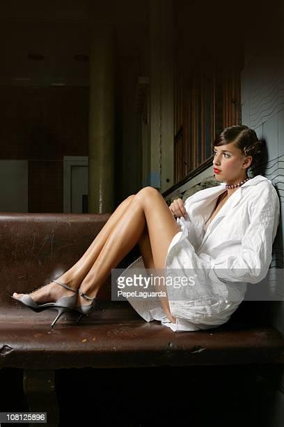 若い女性がポーズをとると木製ベンチに座る