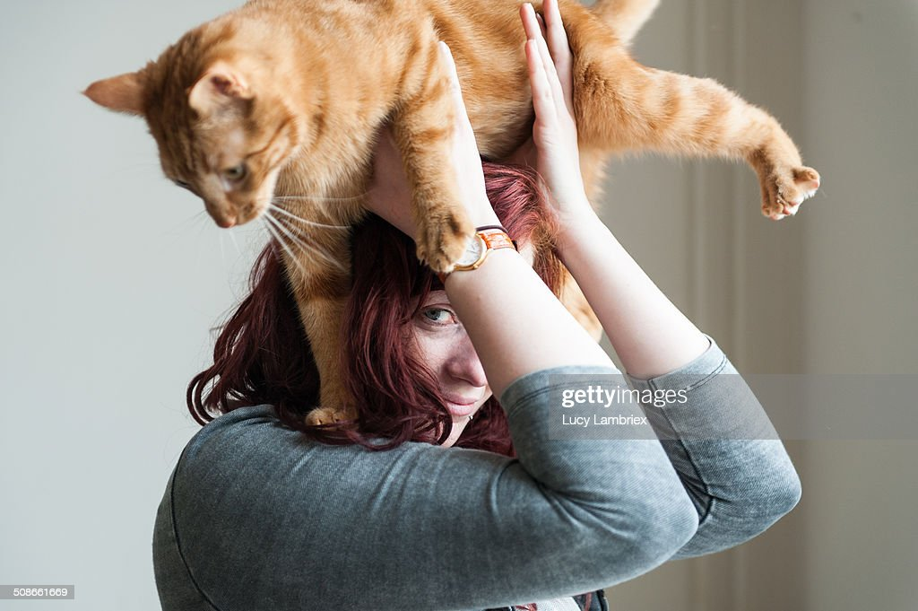 Young woman posing being jumped on by cat.