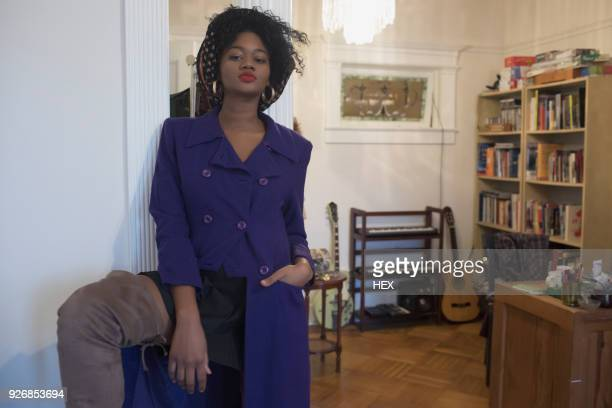 A young woman posing in a purple coat