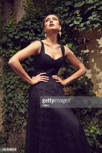 Junge Frau im schwarzen Kleid posieren im Freien