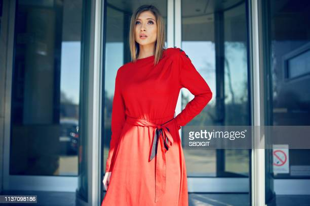 young woman posing in red dress - orange dress stock pictures, royalty-free photos & images