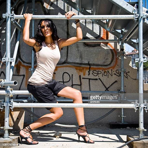 junge frau posieren in stahl-struktur mit graffitti an der wand - junge frau allein stock-fotos und bilder