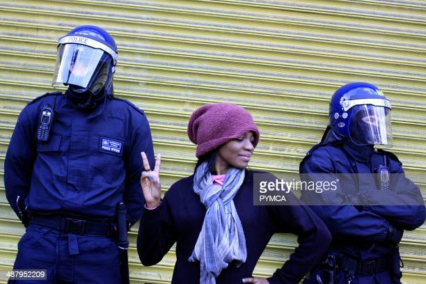 Young woman posing next to riot police in Hackney London during the riots in August 2011
