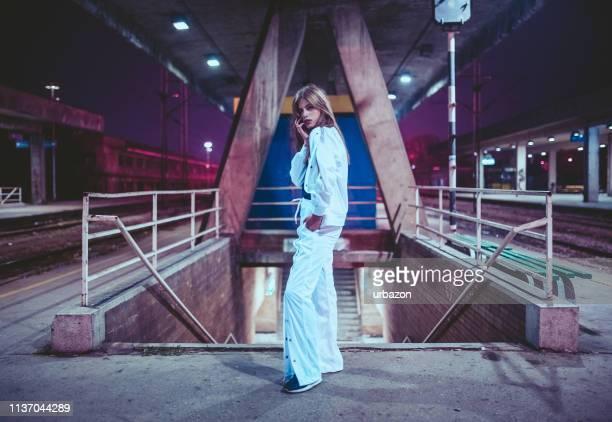 junge frau posiert auf einem bahnhof - trainingsanzug stock-fotos und bilder